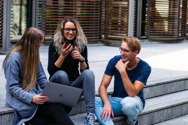 3 studenten op trap buiten met laptop en mobiel