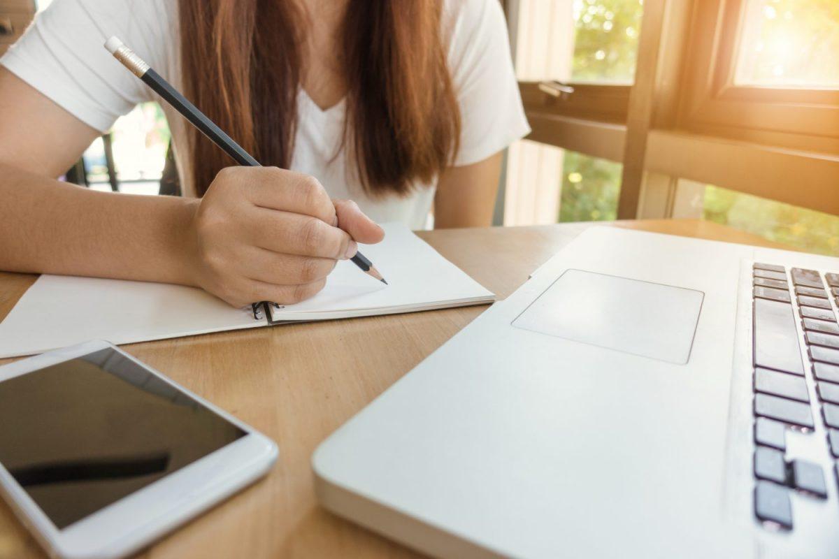 studerend lerend meisje met schrift en laptop en mobiel