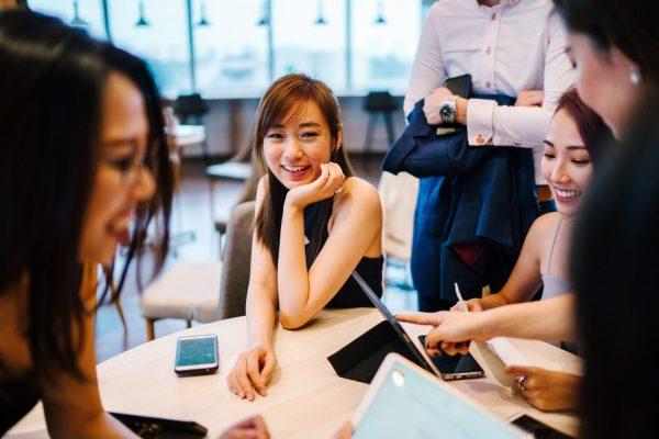 groepje studenten aan tafel met een ipad en mobiel