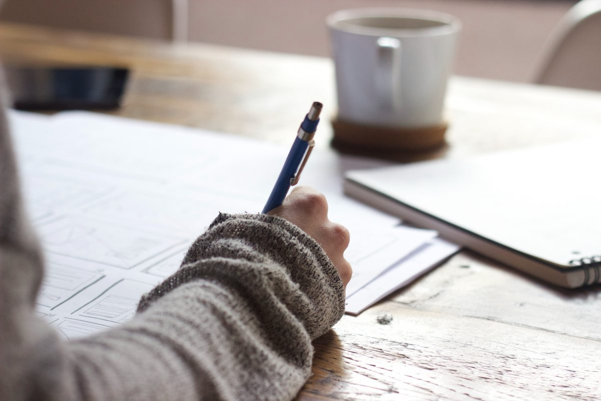 Hand met pen op houten tafel